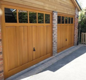 Woodrite Padbury solid cedar wood up and over garage doors in Light Oak finish with plain glazing