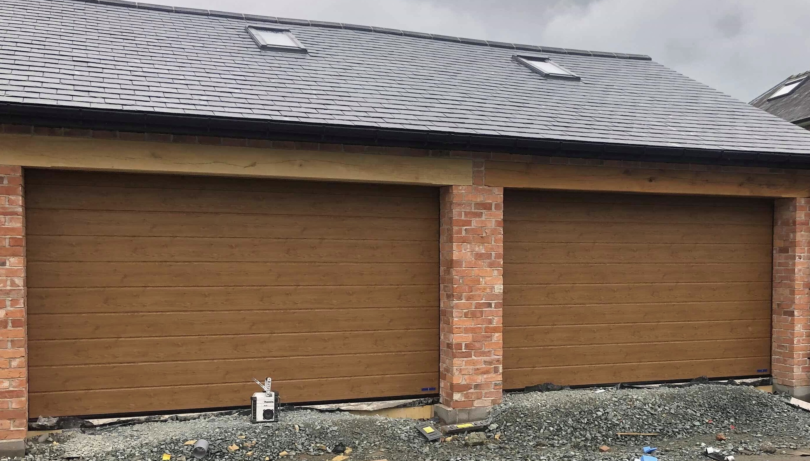 Two insulated sectional garage doors in Golden Oak finish