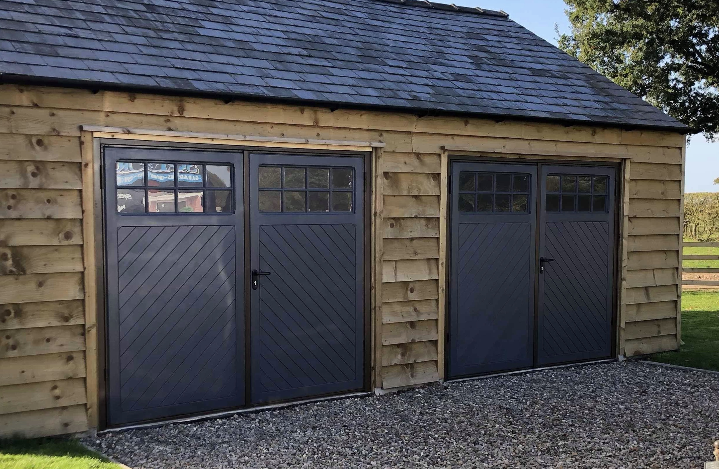 Two pairs of side hinged doors with glazing on a timber garage