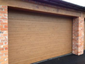 Hormann M rib automatic sectional garage door in Winchester Oak