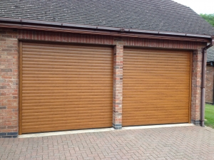 E1: A pair of Aluroll Classic insulated roller shutter garage doors in Golden Oak finish