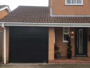 E1: Hormann LPU 42 insulated sectional door in Anthracite Grey with matching TPS700 front entrance door