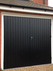 B: Fort side-hinged steel garage door set in standard vertical rib in Jet Black